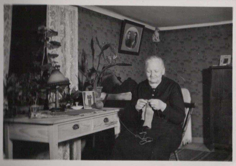 """Tekla Karlsson på besök hos sin syster Hildur Larsson på föräldragården Bågvik 4:2(""""Flinks""""). Hon stickar i en ny häl på en trasig ullstrumpa. Bilden är tagen omkring 1940. Hämtad från http://www.bygdeband.se/sverige/kalmar-lan/vastervik/loftahammar/bagvik/bild/2303311/"""